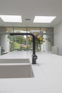 Zwarte kraan met werkblad en spoelbak in solid surface
